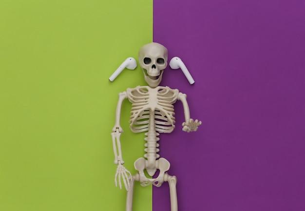 Szkielet i bezprzewodowe słuchawki na zielonym fioletowym tle.