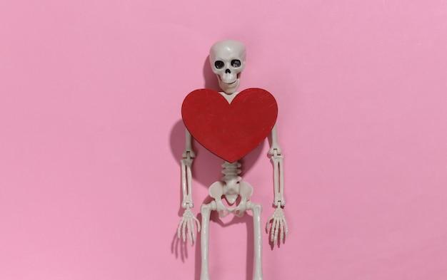 Szkielet i czerwone ozdobne serce na jasnym różowym tle. walentynki lub motyw halloween.