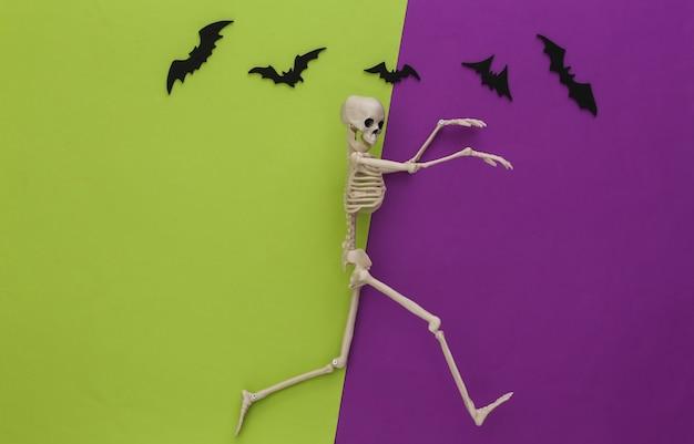 Szkielet i latające ozdobne nietoperze na zielonym, fioletowym papierze. halloweenowa dekoracja, przerażający motyw