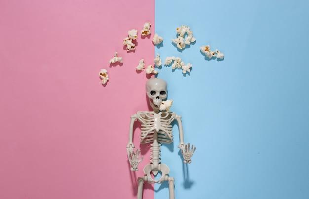 Szkielet i popcorn na różowym niebieskim tle. halloweenowa kompozycja