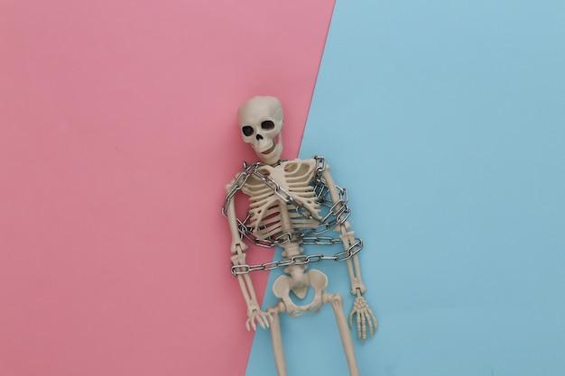 Szkielet owinięty metalowym łańcuszkiem na różowym niebieskim pastelu. halloweenowa dekoracja, przerażający motyw