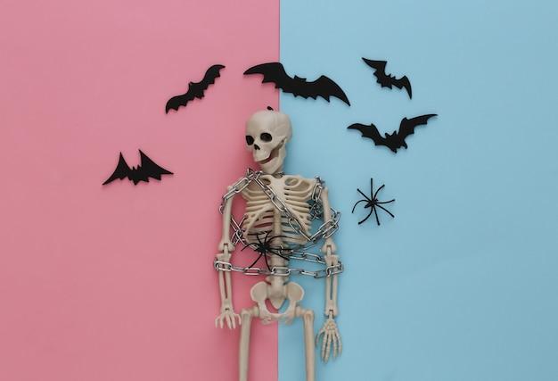 Szkielet owinięty metalowym łańcuszkiem na różowym niebieskim pastelu z nietoperzami i pająkami. halloweenowa dekoracja, przerażający motyw
