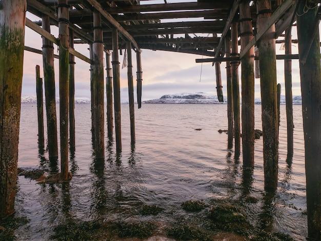 Szkielet szopy rybackiej na plaży. opuszczony dom na tle arktycznego nieba. stara autentyczna wieś teriberka. rosja.