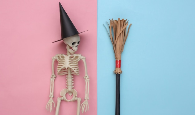 Szkielet w kapeluszu wiedźmy i miotle. niebieskie i różowe pastelowe tło. minimalistyczna koncepcja halloween. widok z góry. płaskie ułożenie
