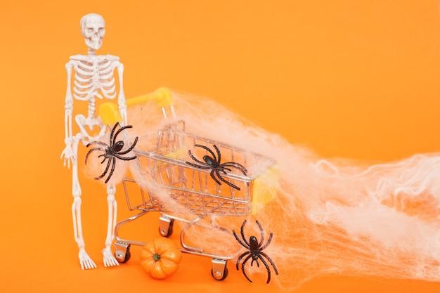 Szkielet z dynią przy wózku pajęczyny i pająki na pomarańczowym tle