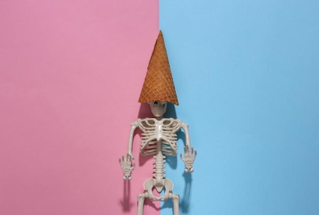 Szkielet z rożki waflowe lody na różowym niebieskim jasnym tle. minimalizm halloweenowa kompozycja