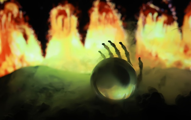 Szkielet zombie ręka wznosząca się z cmentarza - halloween. tajemnicze prognozy magicznej kuli i dym na ciemnej scenie. wróżka, siła umysłu, koncepcja przewidywania. tajemnicze tło