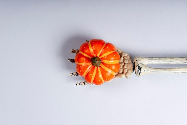 Szkieletowe ramię trzyma dyni.