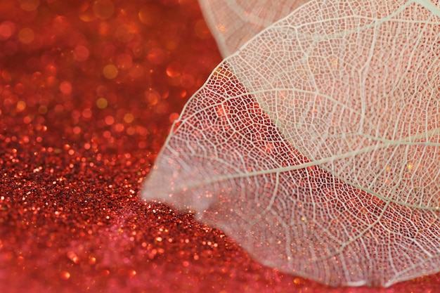 Szkieletowy liść na tle czerwonego brokatu z błyszczącym bokehtapeta telefon lśniący brokatem piękne tło natury z lśniącym bokeh