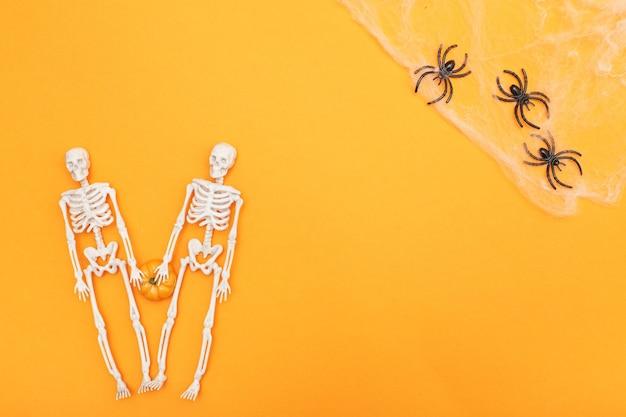 Szkielety z dyniową pajęczyną i czarnymi pająkami na pomarańczowym tle