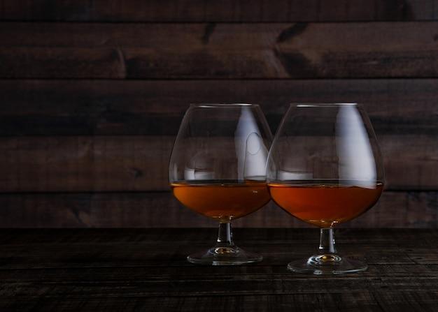 Szkła brandy koniak strzelali na drewnianym stołowym tle