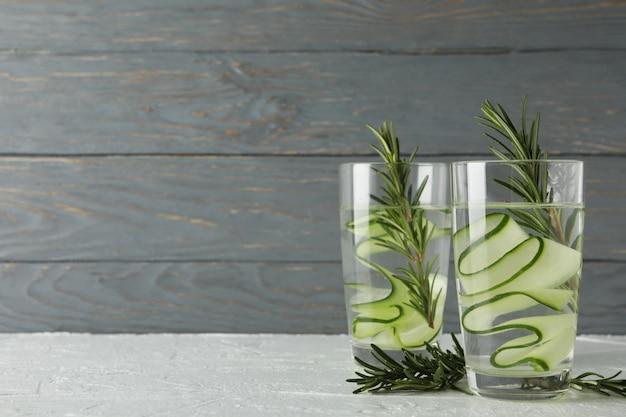Szkła z ogórek wodą na bielu stole