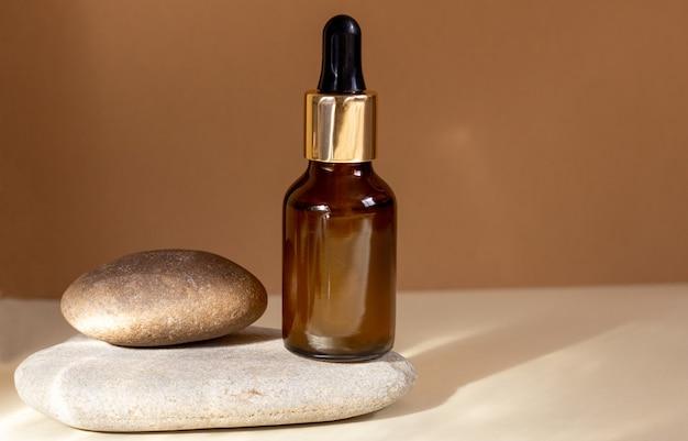 Szklana buteleczka kosmetyku z zakraplaczem stoi na kamieniu na beżowym tle w jasnym świetle słonecznym.