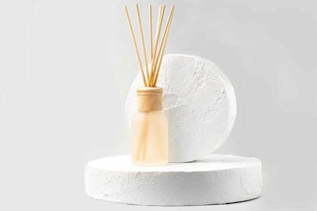 Szklana butelka aromatu i drewniane kije pozostające na podium cementu biały na białym tle.