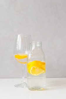 Szklana butelka i szklany kielich z wodą i cytryną na jasnym tle. lemoniada, sok z cytryny, cytrusy, pomarańcze, witaminy, dieta, detoks, oczyszczanie, smoothie, świeży poranek, woda