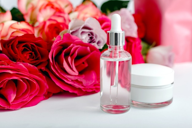Szklana butelka kosmetyczna, krem, serum, olej na tle kwiatów biały stół. kwiat czerwony różowy róż naturalny organiczny produkt kosmetyczny. spa, pielęgnacja skóry, kąpiele na ciało. zestaw kosmetyków z różą.