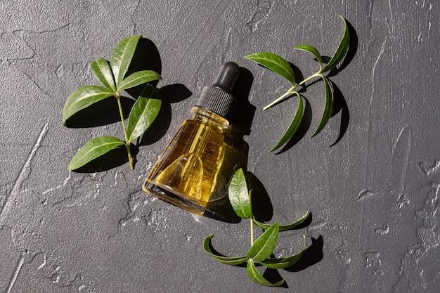 Szklana butelka kosmetyczna z serum lub olejkiem do twarzy na ciemnym tle z zielonymi ziołami. koncepcja ekologicznych produktów kosmetycznych. skopiuj miejsce.