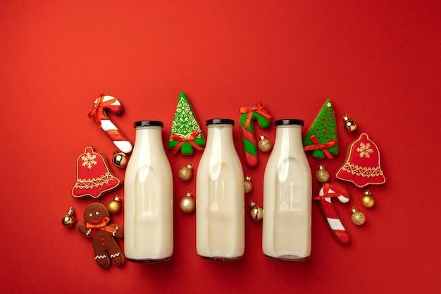 Szklana butelka mleka i świąteczne pierniki na czerwono