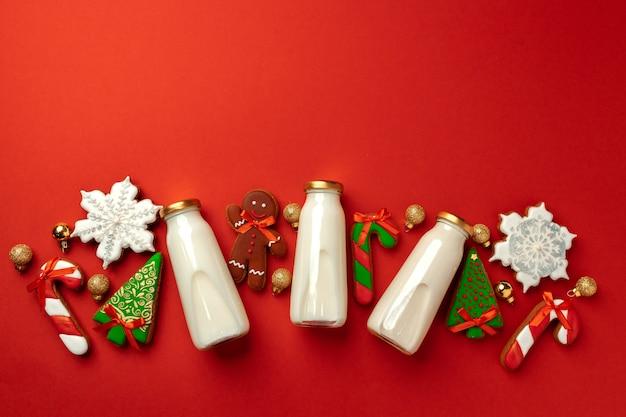 Szklana butelka mleka i świąteczne pierniki na czerwonym tle