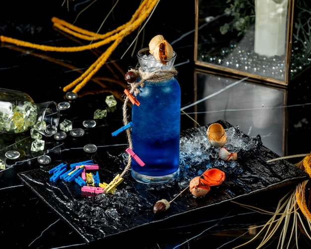 Szklana butelka niebieskiej laguny ozdobiona liną i kolorową bielizną