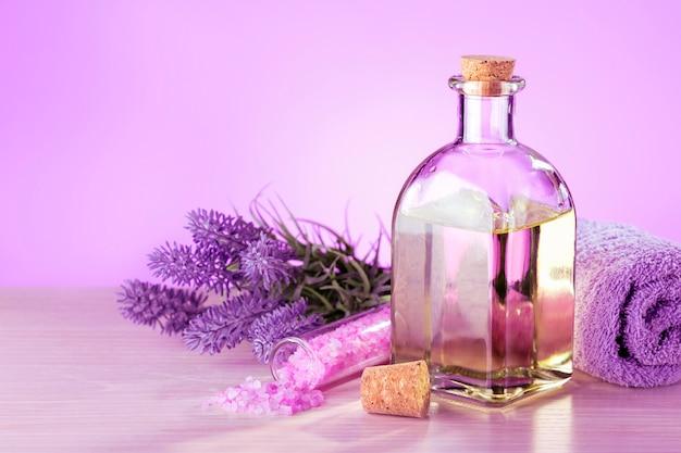 Szklana butelka olejku lawendowego ze świeżymi kwiatami lawendy i solą morską na stole. koncepcja spa.