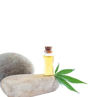 Szklana butelka oleju konopnego i liść konopi na białym tle
