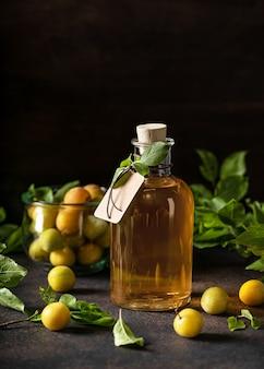 Szklana butelka pysznego żółtego likieru śliwkowego lub wina na drewnianym stole