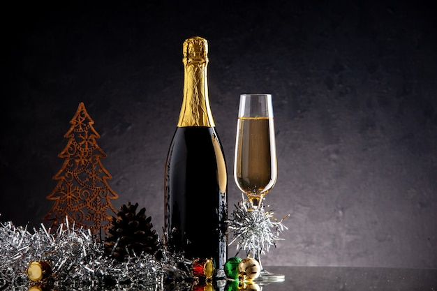 Szklana butelka szampana z widokiem z przodu ozdoby świąteczne na ciemnej powierzchni