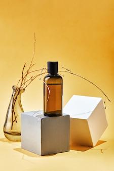 Szklana butelka szamponu lub odżywki do pielęgnacji ciała na geometrycznych kształtach i wysuszonej gałązce. naturalne ekologiczne ekologiczne kosmetyki spa koncepcja urody.