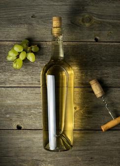 Szklana butelka wina z korkami na drewnianym stołowym tle