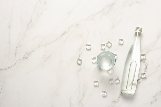 Szklana butelka wody, szkło z wodą i kostki lodu na marmurowym stole.