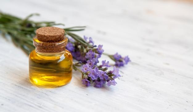 Szklana butelka wypełniona olejkiem lawendowym. kosmetyki naturalne, koncepcja ziołolecznictwa