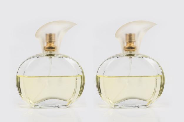 Szklana butelka wypełniona perfumami na białym tle