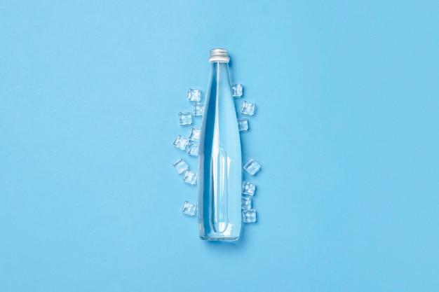Szklana butelka z czystą wodą na niebieskiej powierzchni z kostkami lodu. pojęcie zdrowia i urody, bilans wodny, pragnienie, upał, lato. leżał płasko, widok z góry.