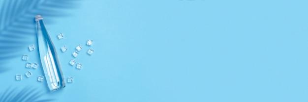 Szklana butelka z czystą wodą na niebieskim polu z kostkami lodu. pojęcie zdrowia i urody, bilans wodny, pragnienie, upał, lato. widok płaski, widok z góry. transparent.
