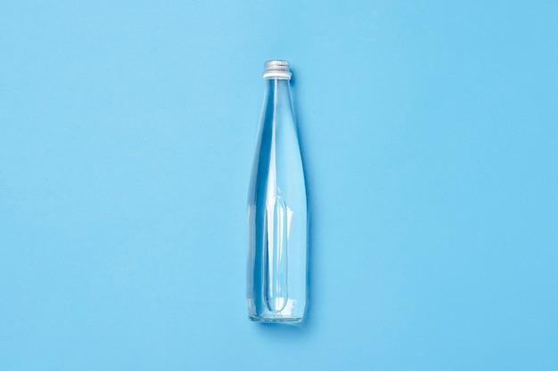 Szklana butelka z czystą wodą na niebieskim tle. pojęcie zdrowia i urody, bilans wodny, pragnienie, upał, lato. płaski świecki, widok z góry.