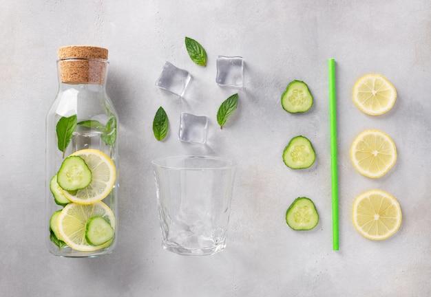 Szklana butelka z infuzowaną wodą z cytryną, ogórkiem, miętą i kostkami lodu