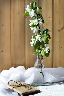 Szklana butelka z kwitnących gałęzi wiśni, jabłoń na drewnianym tle. kompozycja kwiatowa w słoneczny dzień wiosny.