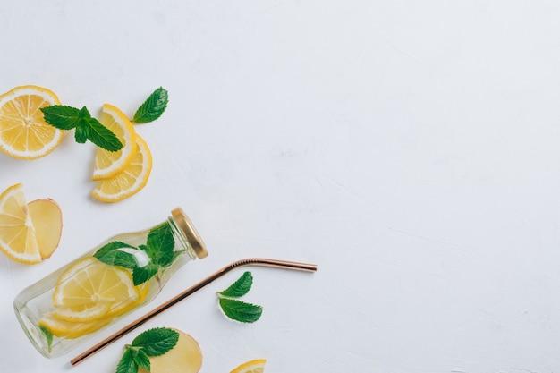 Szklana butelka z lemoniadą z metalową słomką i składnikami do gotowania. imbir, cytryna, mięta na białej powierzchni. płaski świeckich, widok z góry. skopiuj miejsce