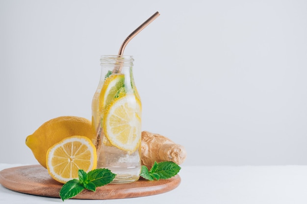 Szklana butelka z lemoniadą z metalową słomką na drewnianej tacy. imbir, cytryna, mięta na białym tle. skopiuj miejsce
