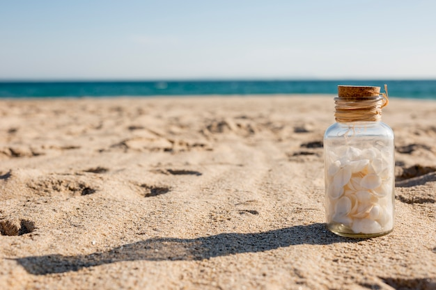 Szklana butelka z muszelkami na piasku