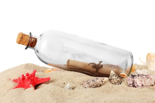 Szklana butelka z notatką wewnątrz na piasku na białym tle
