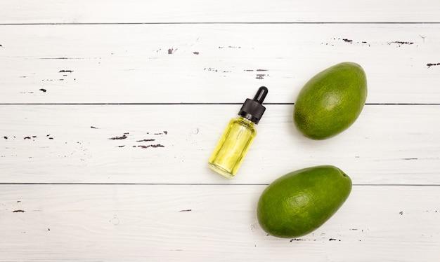 Szklana butelka z pipetą i olejem z awokado i owocem awokado na jasnym drewnianym tle, widok z góry, wolne miejsce na tekst