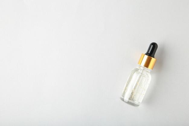 Szklana butelka z pipetą z olejkiem, serum na szarej powierzchni z miejscem na kopię