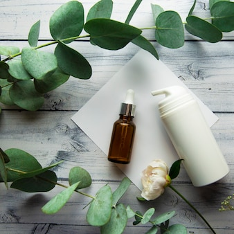 Szklana butelka z serum hialuronowym i butelkami kosmetycznymi leżą na jasnym drewnianym tle otoczki