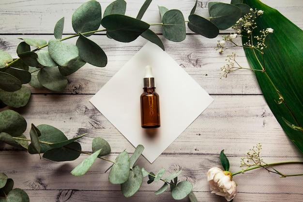 Szklana butelka z serum hialuronowym leży na białym kwadracie na drewnianym tle otoczonym gałązkami eukaliptusa i roślinami produkt kosmetyczny