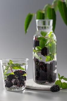 Szklana butelka z wodą smakową z jeżynami i miętą