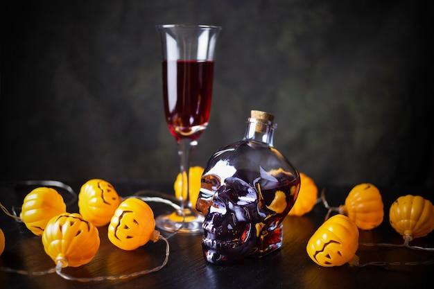 Szklana czaszka butelki, kielich czerwonego wina i pomarańczowa girlanda z lampkami w formie lampionu jack