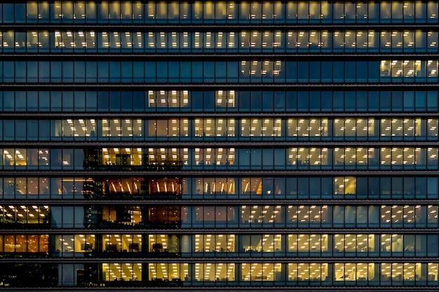 Szklana fasada zewnętrzna z wewnętrznym żółtym oświetleniem świeci na każdym piętrze w wieżowcu