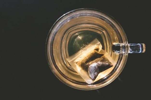 Szklana filiżanka herbata z torbą na ciemnym tle
